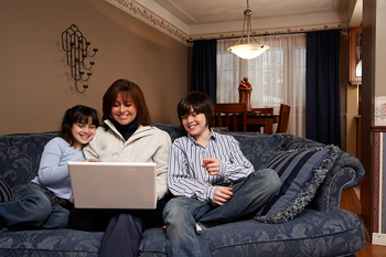 Mother and children on couch with laptop