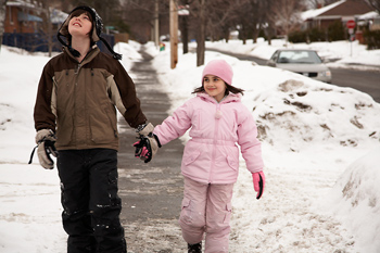 Brother and sister walking on sidewalk in winter