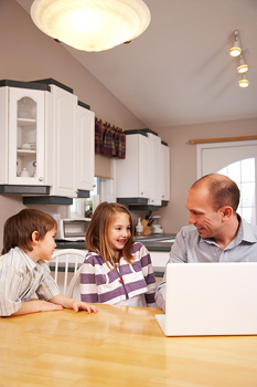 Children and father with laptop on dining room table