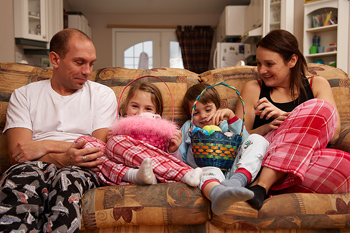 Family on sofa at home with Easter baskets