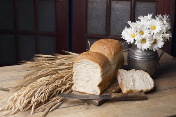 Homemade loaf of bread by wheat and vase of daisies
