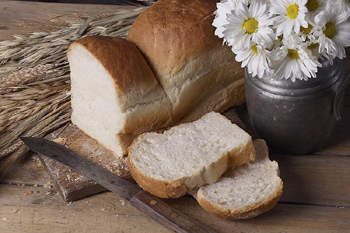 Daisies in jug and bread loaf