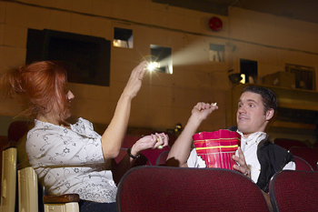 Couple throwing popcorn in movie theater