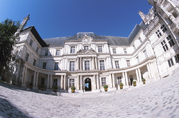 Facade of historical building with cobblestone plaza
