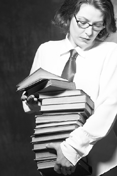 Serious woman carrying stack of books