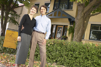 Couple posing by new house