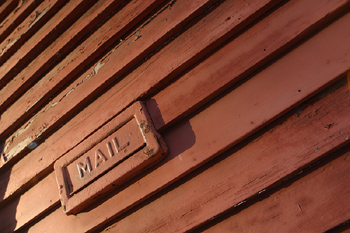 Mail slot on wooden siding