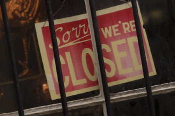 Closed sign behind bars in store window