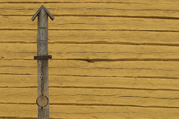 Hitching post by a wooden wall