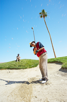 Golfer swinging from sand trap