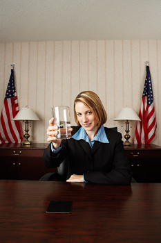 Businesswoman holding out glass of water
