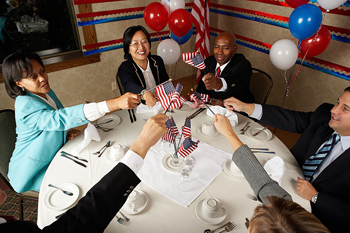 People putting American flags together at table