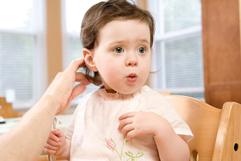 Toddler in highchair being groomed by adult