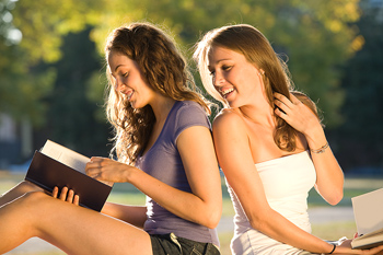 Two women with books sitting back to back outdoors