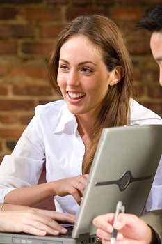Smiling businesswoman at meeting with laptop