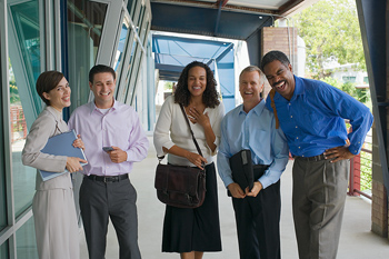 Laughing businesspeople posing together outdoors