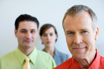 Man posing with other office staff