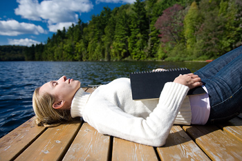 Woman with book basking on dock in lake