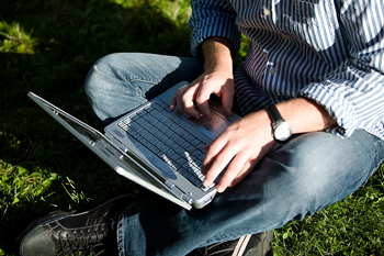Man sitting on lawn with laptop computer