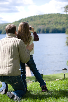 Father and daughter with binoculars at lake