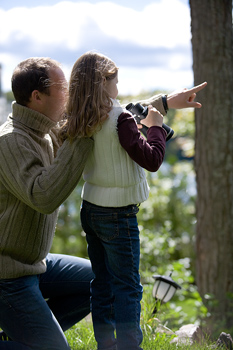 Father and daughter birdwatching outdoors