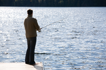 Man fishing from dock on the water