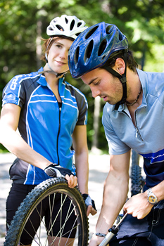 Couple inflating tire on mountain bike