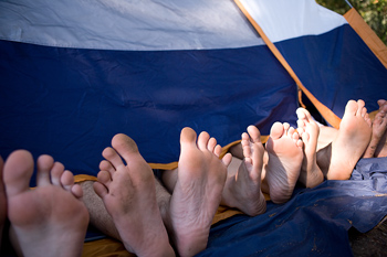 Feet of five people protruding from tent
