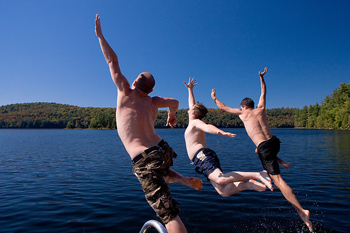 Three men jumping into lake from dock
