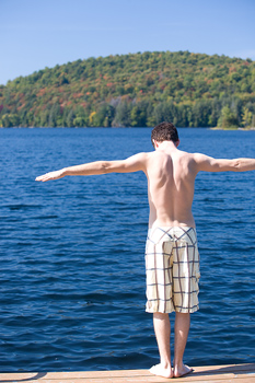 Back view of man in diving pose on dock by lake