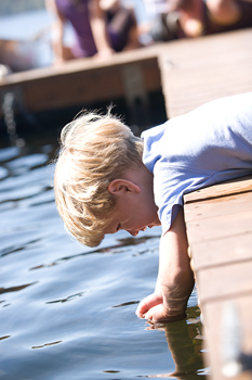 Curious boy lying on dock with hands in water