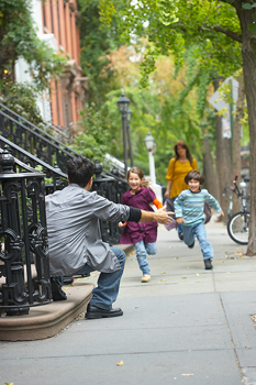 Children running to waiting father in residential neighborhood