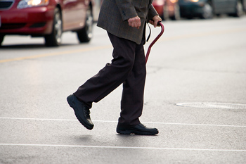 Person crossing street with cane
