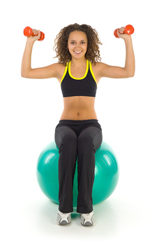 Woman sitting on exercise ball and lifting weights