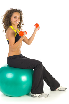 Woman lifting weights atop exercise ball