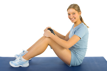 Woman sitting and posing on exercise mat
