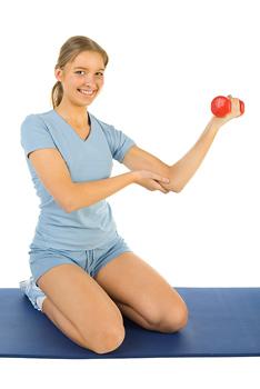 Woman sitting on mat and lifting dumbbell