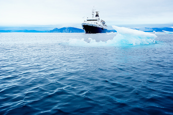 Approaching cruise ship with icebergs in Arctic Ocean