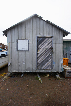 Weathered exterior of shack with aluminum siding