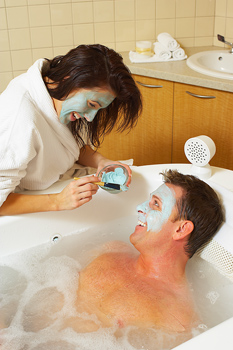 Playful couple giving and receiving facial treatment at spa