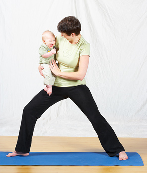 Woman in yoga pose holding baby