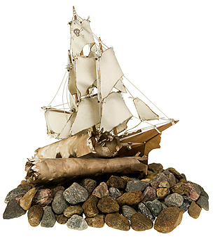 Model pirate ship with scrolls on gravel pile
