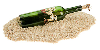 Message in a bottle on pile of sand