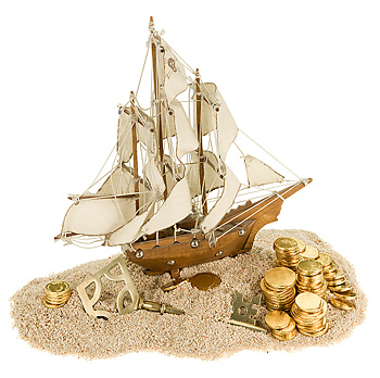 Miniature replica of pirate whip with coins on pile of sand