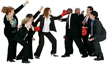 Businesswoman boxing businessman with others