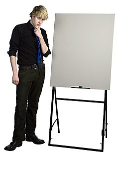 Businessman in thoughtful pose by blank board