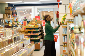 Woman reading label of product in health foods store