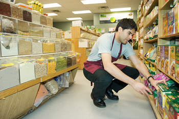 Crouching employee stocking grocery shelves