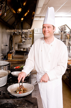 Chef preparing meal on stove in restaurant kitchen