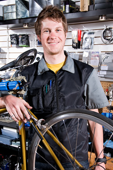 Man posing with bike in bicycle shop